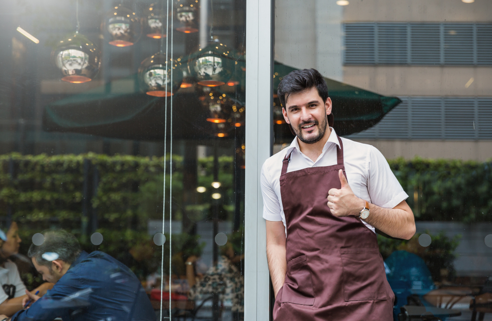 """Latino small business owner giving thumbs up in front store to express the idea """"successful small business"""""""