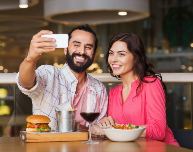 Hispanic couple taking selfie with smartphone and and using Snapchat in a restaurant
