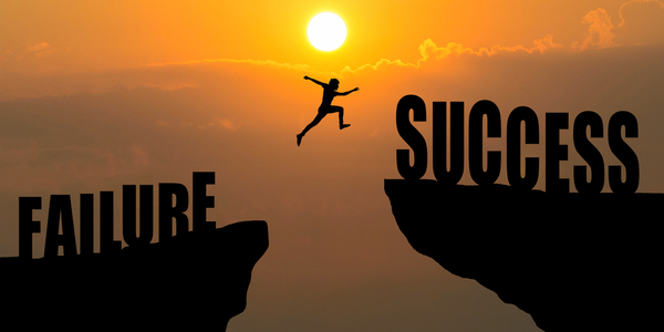 """Man jumping over cliff with words """"Failure"""" and """"Sucess"""", to illustrate the idea of overcoming fear or """"superar el miedo"""""""